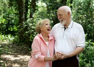 A happy, active senior couple laughing together on a walk through the park. She's wearing a hearing aid.